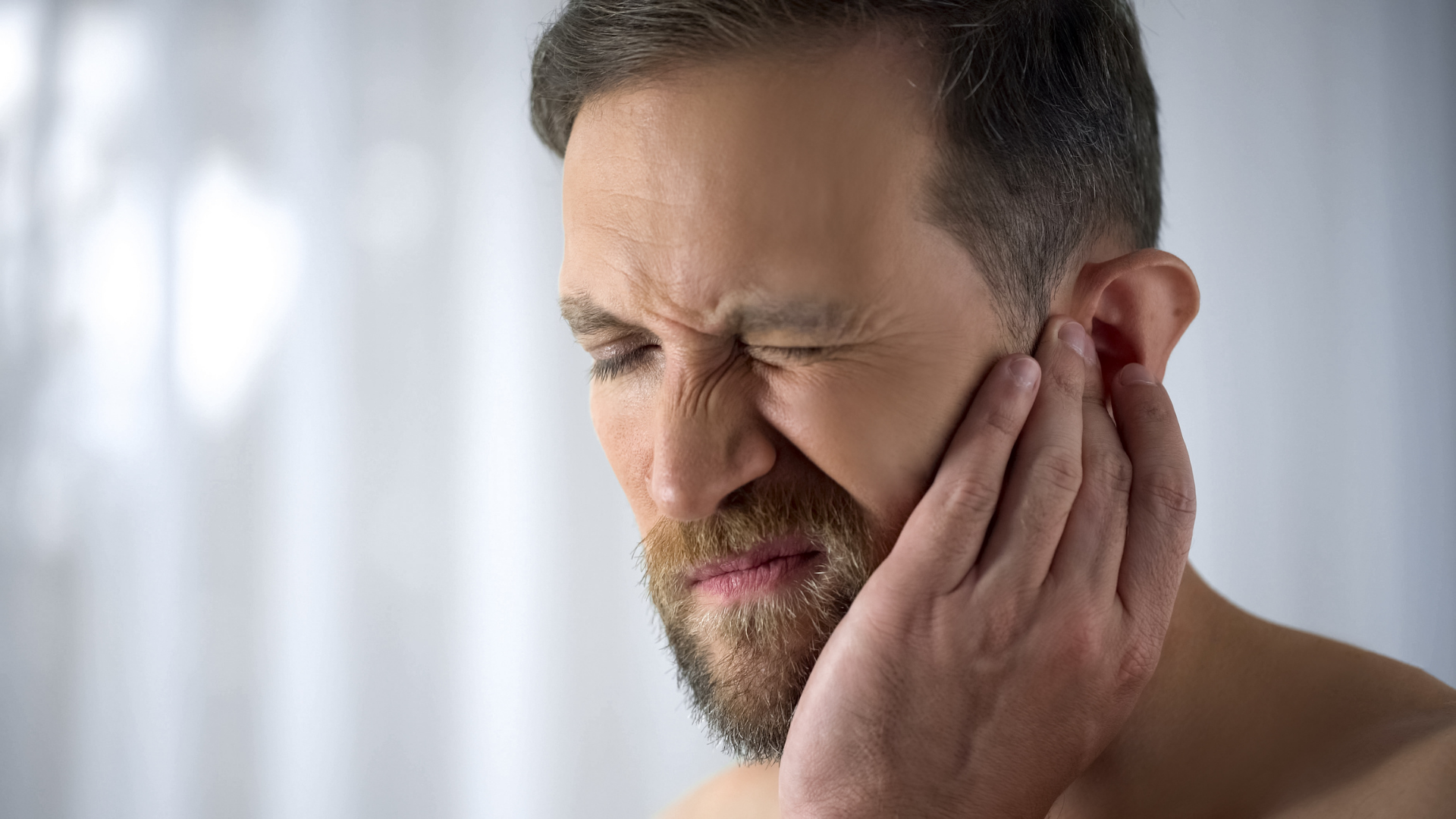 man suffering with hearing loss