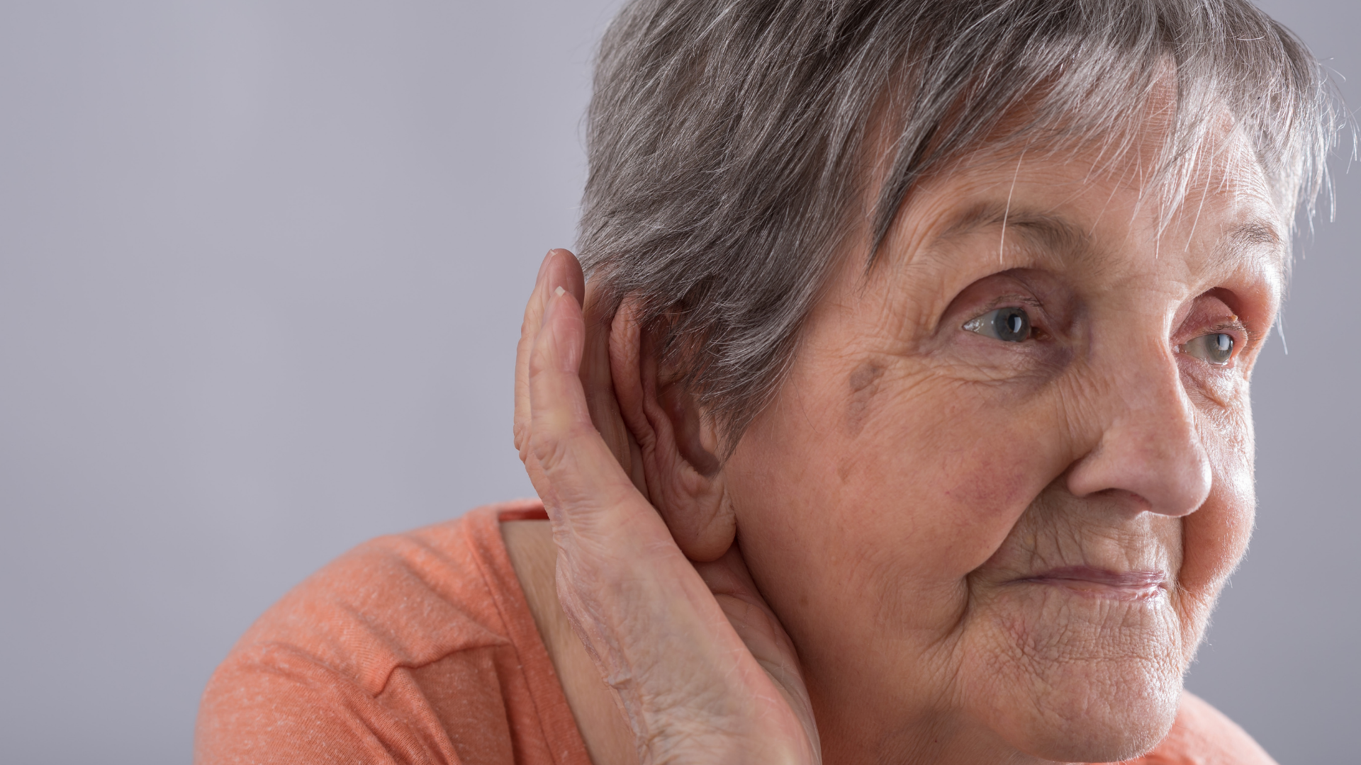 old woman holding her ear